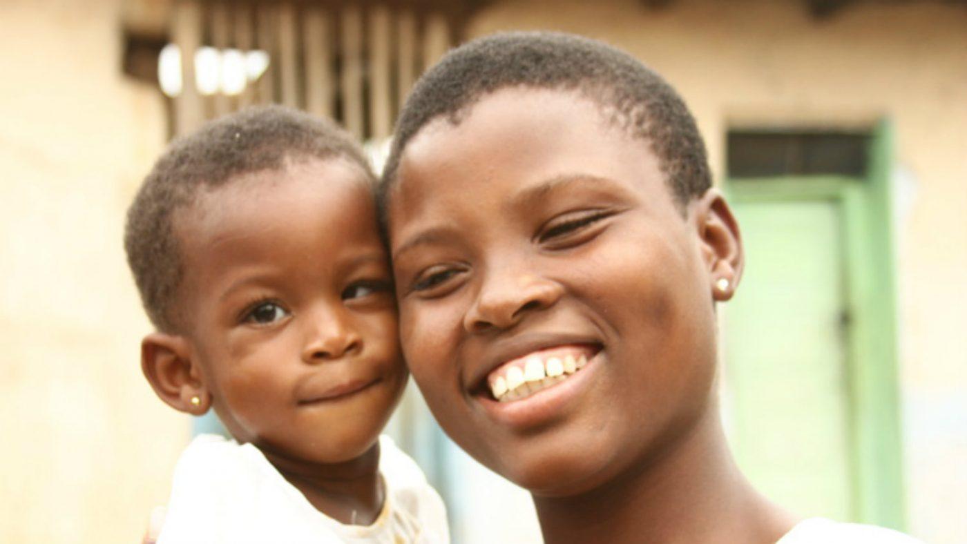 En mor smiler med sitt barn.
