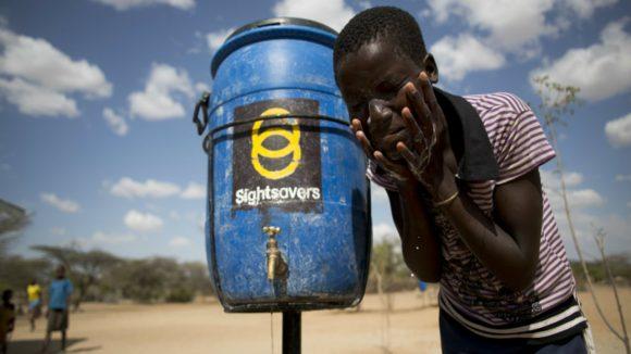 En gutt bruker rent vann fra en Sightsavers-anlegg.