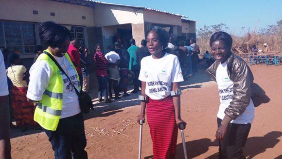 To kvinner snakker med mennesker med funksjonshemninger.