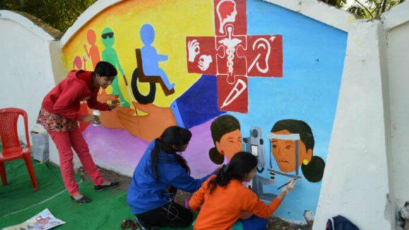 Tre barn maler en veggmaleri på veggen.