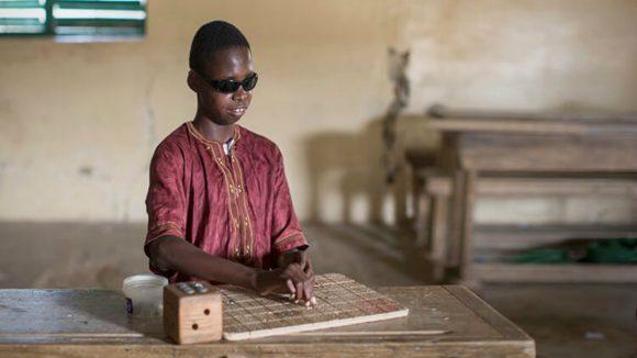 En ung gutt leser blindeskrift i et klasserom.