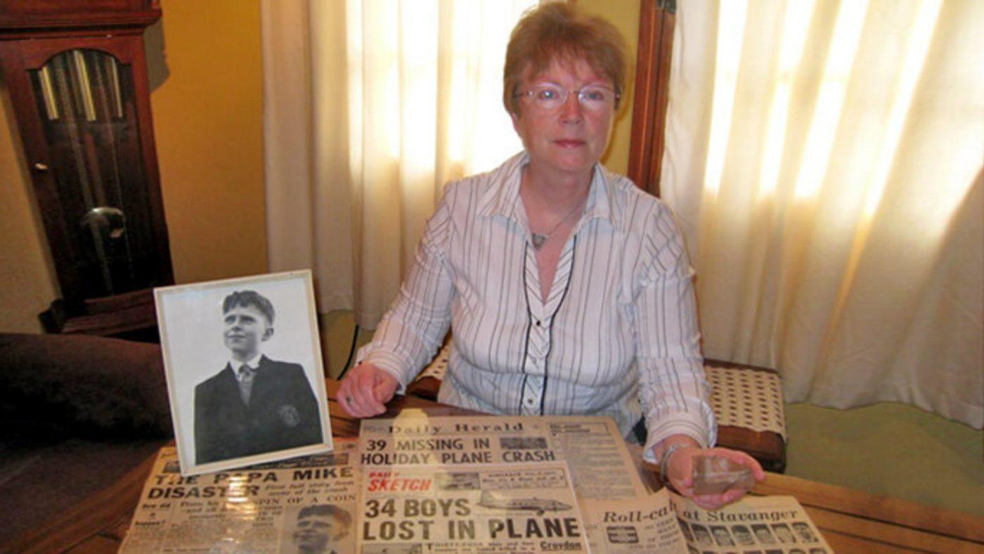 Rosalind sitter ved et bord som viser fotografier og aviser.