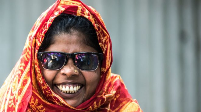 En kvinne met blindhet smiler mot kamera.