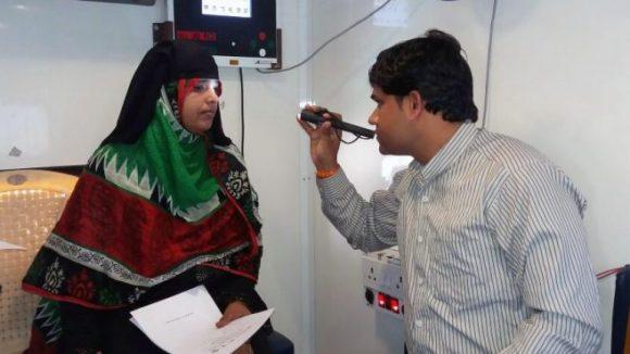 En lege undersøker øynene til en kvinne.