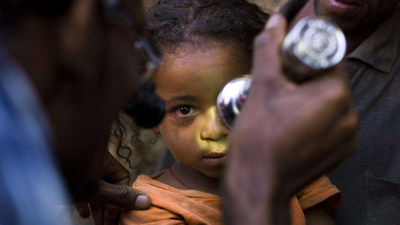 En kvinne undersøker en barn.