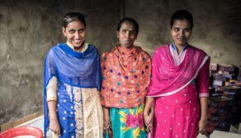 Tre kvinne smiler mot kamera.
