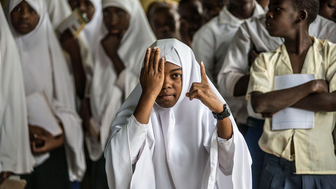 En jente dekker ene øyet med ene hånden, og peker mot synstavlen med den andre hånden.