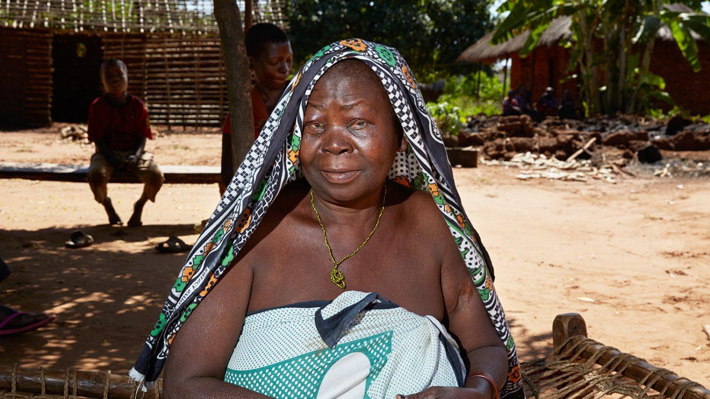 Agnes sitter utenfor hjemmet sitt i Tanzania.