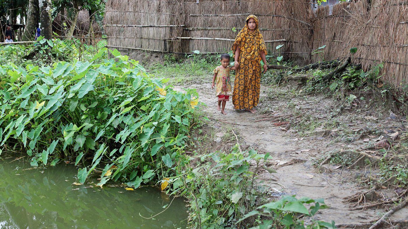 Aklima holder morens hånd når de går forbi en damm i nærheten av hjemmet deres.