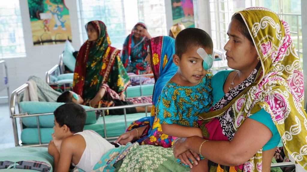 Aklimas mor holder henne i armene sine etter hennes grå stær-operasjon. Hun har en grønn plastikk-kopp tapet til ansiktet, som beskytter øyet hennes.