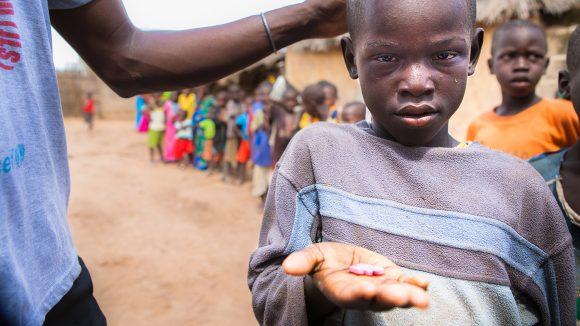 En ung gutt holder hånden sin opp mot kameraet, og viser frem trakom-medisinene han holder.