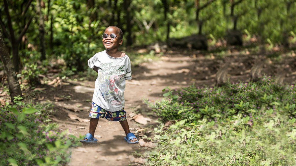 Criscent er stolt ikledd sine nye briller mens han står i skogen på vei til landsbyen sin i Uganda.