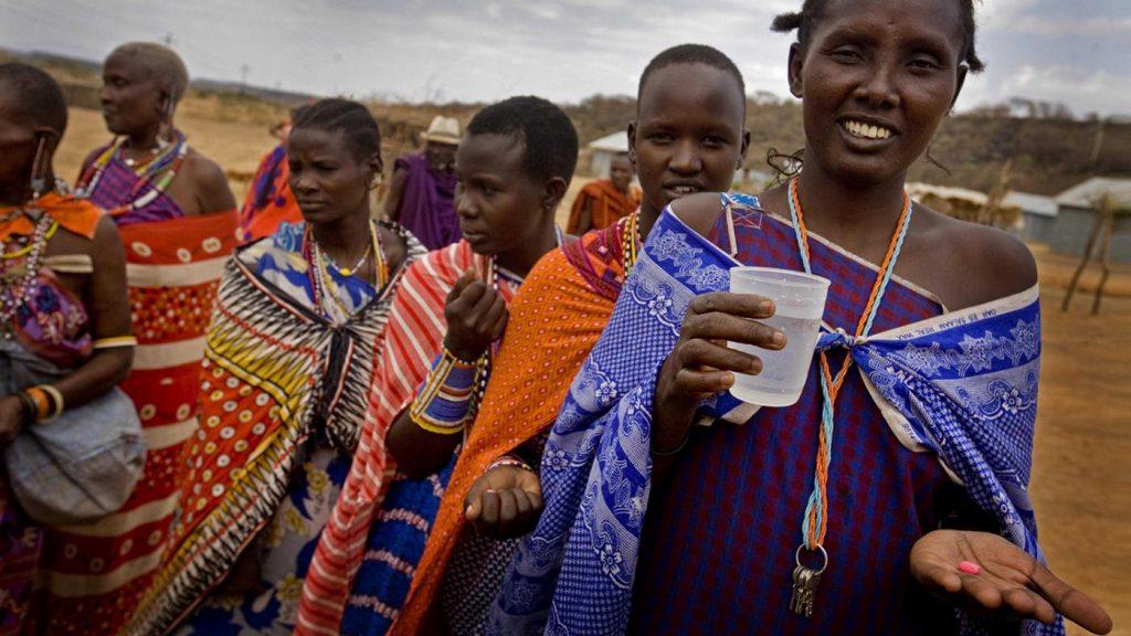 En gruppe landsbyboere venter på å motta medisin fra den lokale legemiddeldistributøren, som gir dem en kopp med tablettene.