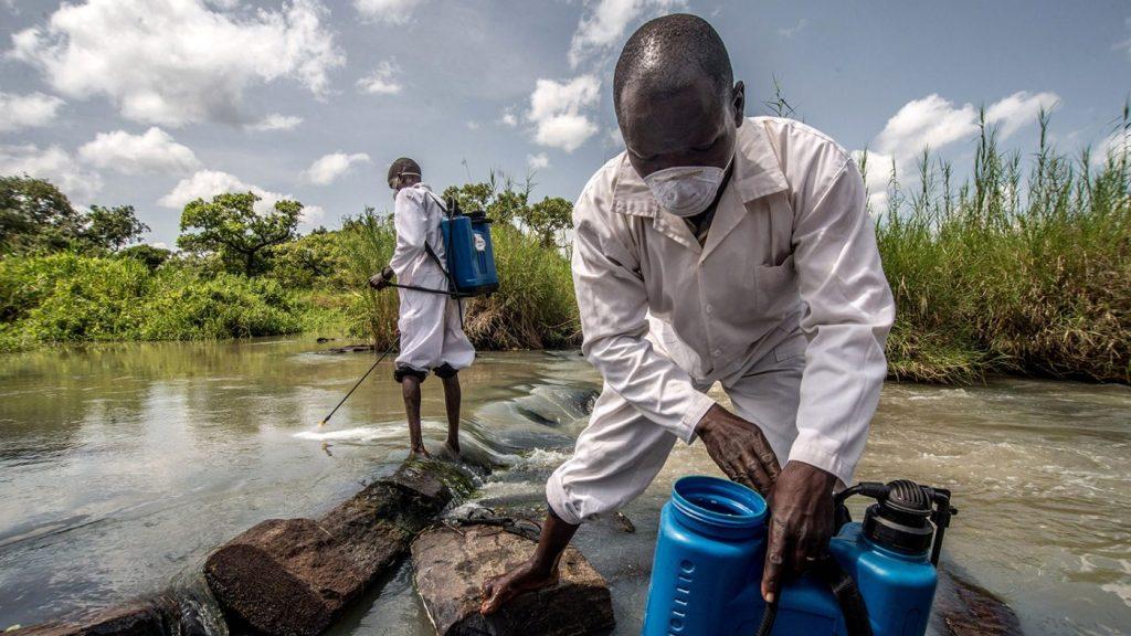 To feltarbeidere behandler elvevannet i Uganda.