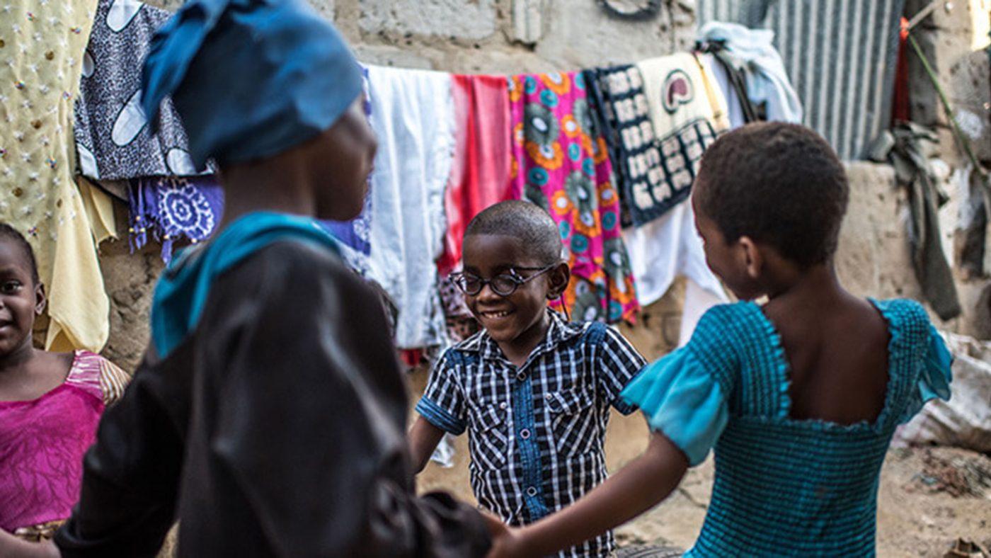 Saidi holder hender med sine kusiner mens de danser rundt i en sirkel.
