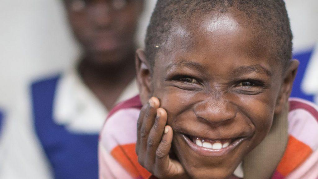En ung gutt som smiler.