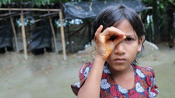 En ung jente former hånden som en trakt rundt øyet for å prøve å se bedre.