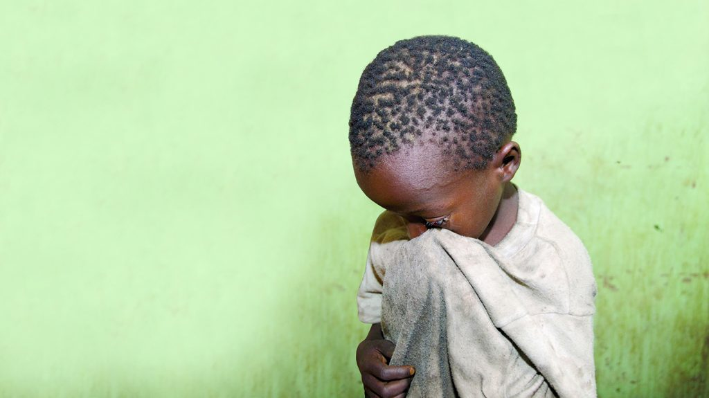 En ung gutt tørker øynene sine på t-skjorten.