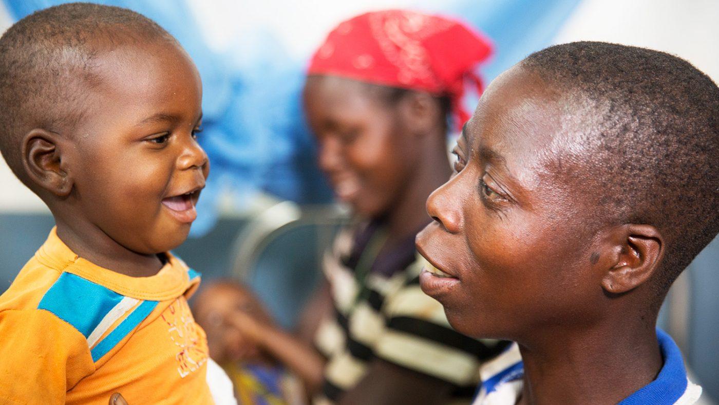 en barn smiler mot en kvinne.