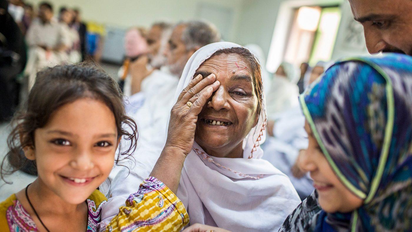 Zamurrad holder en hånd opp mot øyet, mens både hun og datteren smiler mot kamera.