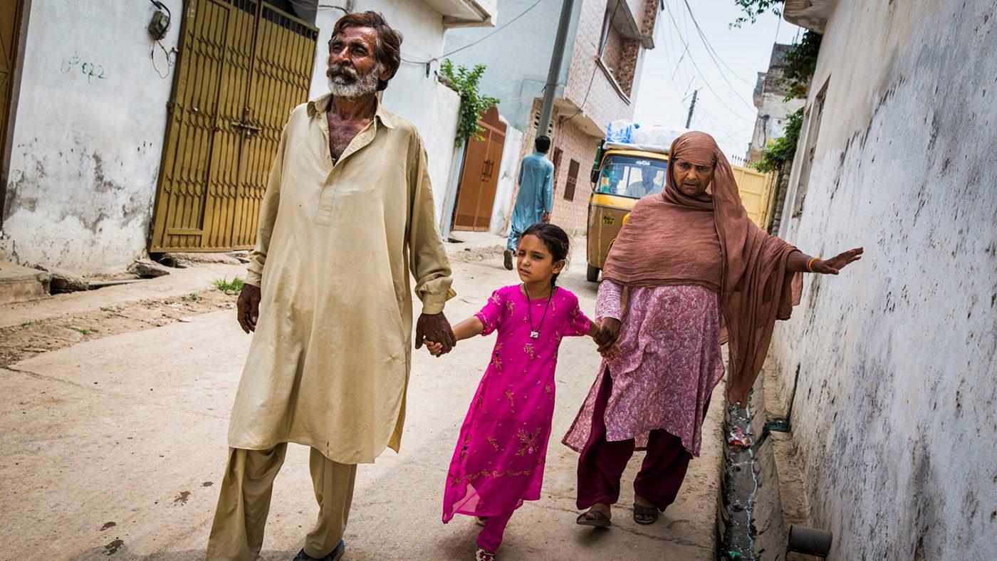 Zamurrad holder en vegg med den ene hånden og ledes av datteren med den andre.