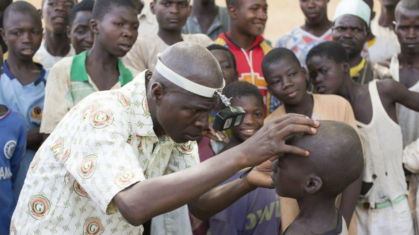 En helsearbeidere undersøker øynene til Abdu.
