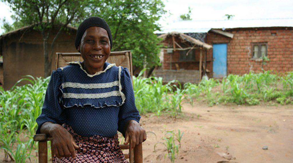 Agnes sitter i landsbyen hennes og smiler.