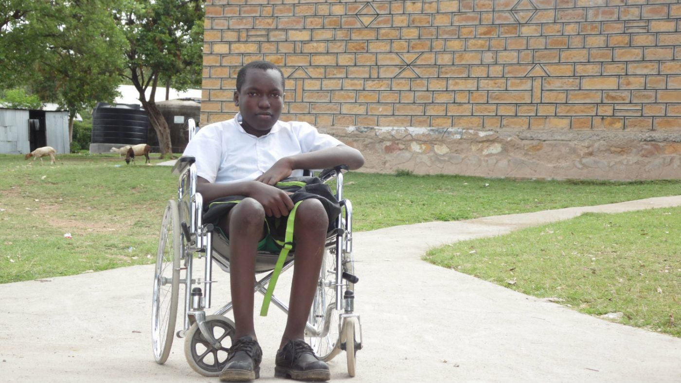 Flash, i rullestolen, utenfor skolen sin.