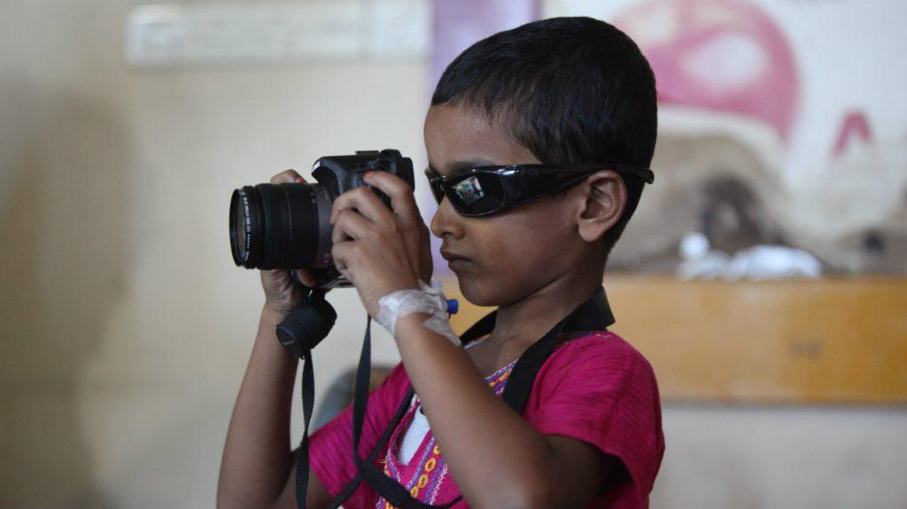 Mehidi, med solbriller på, spiller med et kamera.