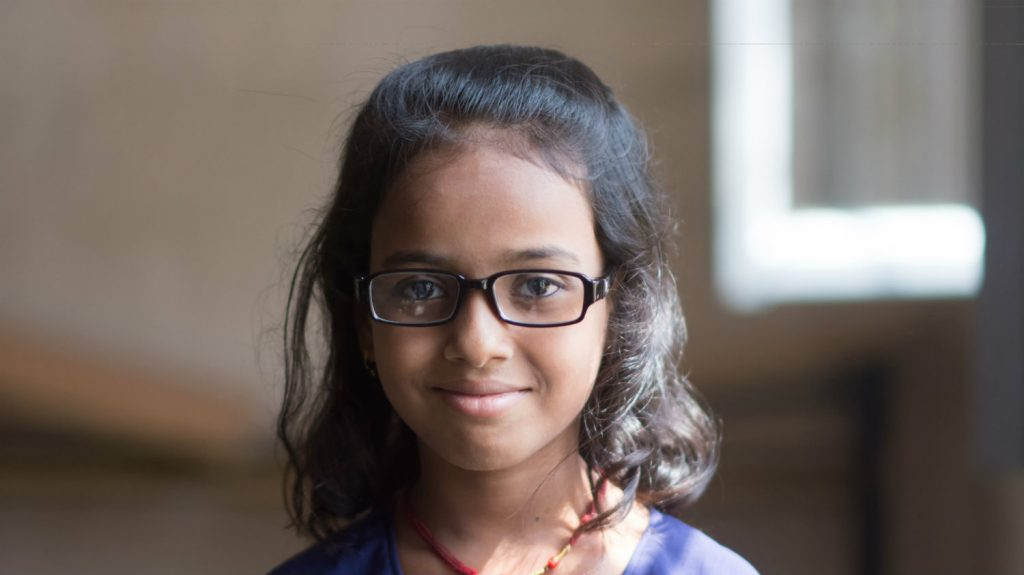Riya, med briller på, smiler.
