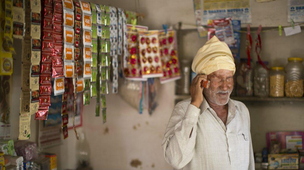 en blind mann snakker på mobilen