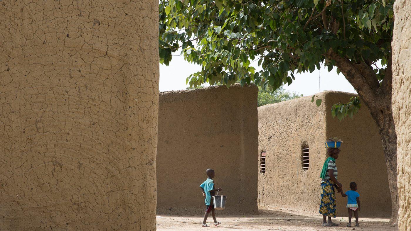 Folk går gjennom to leirbygninger i landsbyen der Sayon bor i Mali.