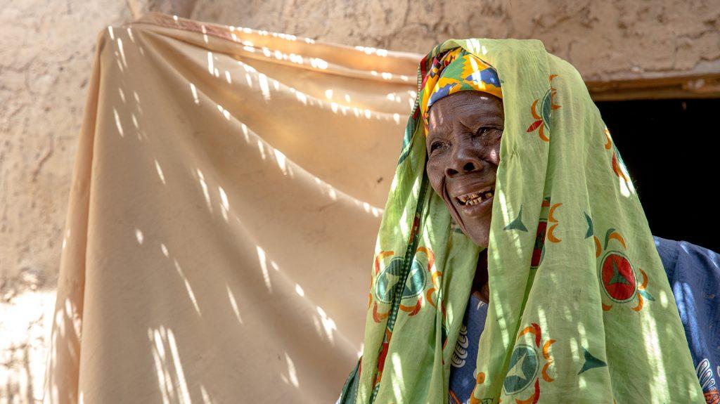 En smilende Sayon, hun sitter utenfor i skyggen.