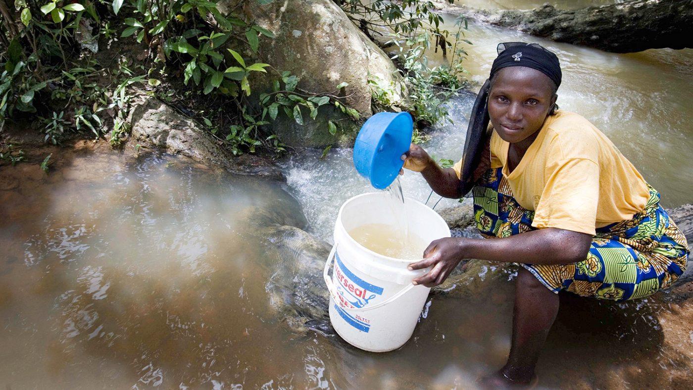 En kvinne sitter i en bekk og bruker en bøtte for å samle vann i Nigeria.