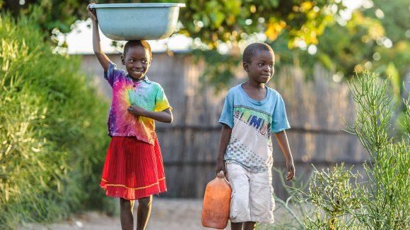 Namukolo og broren hennes bærer vann gjennom landsbyen.