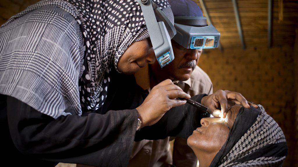 En øyehelsearbeider undersøker en kvinnes øyne for tegn på trakom.