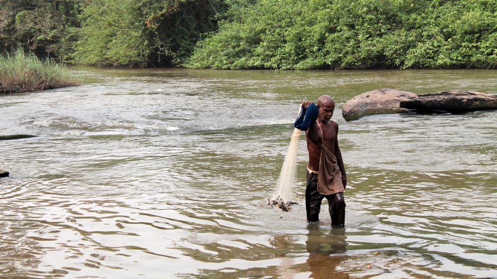 Emmanuel fisker i Pru-elven: han står i knehøyt vann og holder et fiskenett.