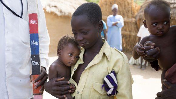 En gutt og lillebroren hans venter på å få medisin som behandler forsømte tropesykdommer i Nigeria.