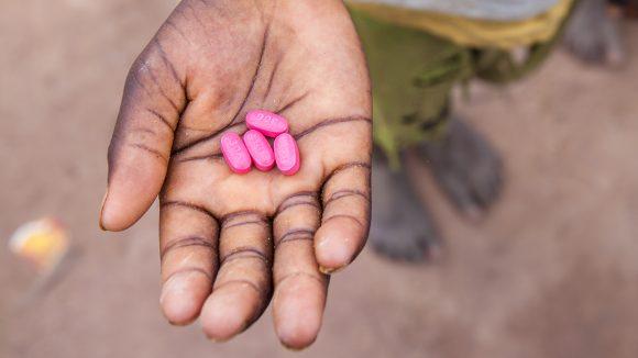 Et barn i Senegal holder Zithromaxtabletter i hånden.