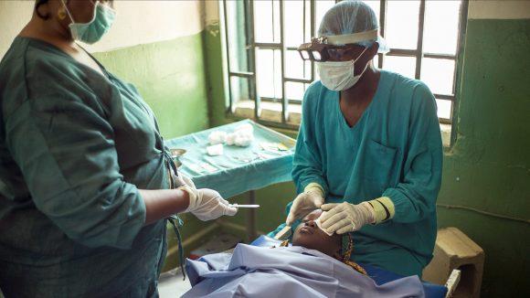 Kirurger opererer en trakompasient.