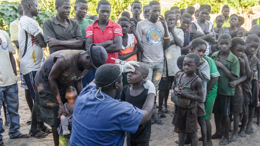Mr Ndalela sitter på kne og undersøker øynene til små barn som står i kø.
