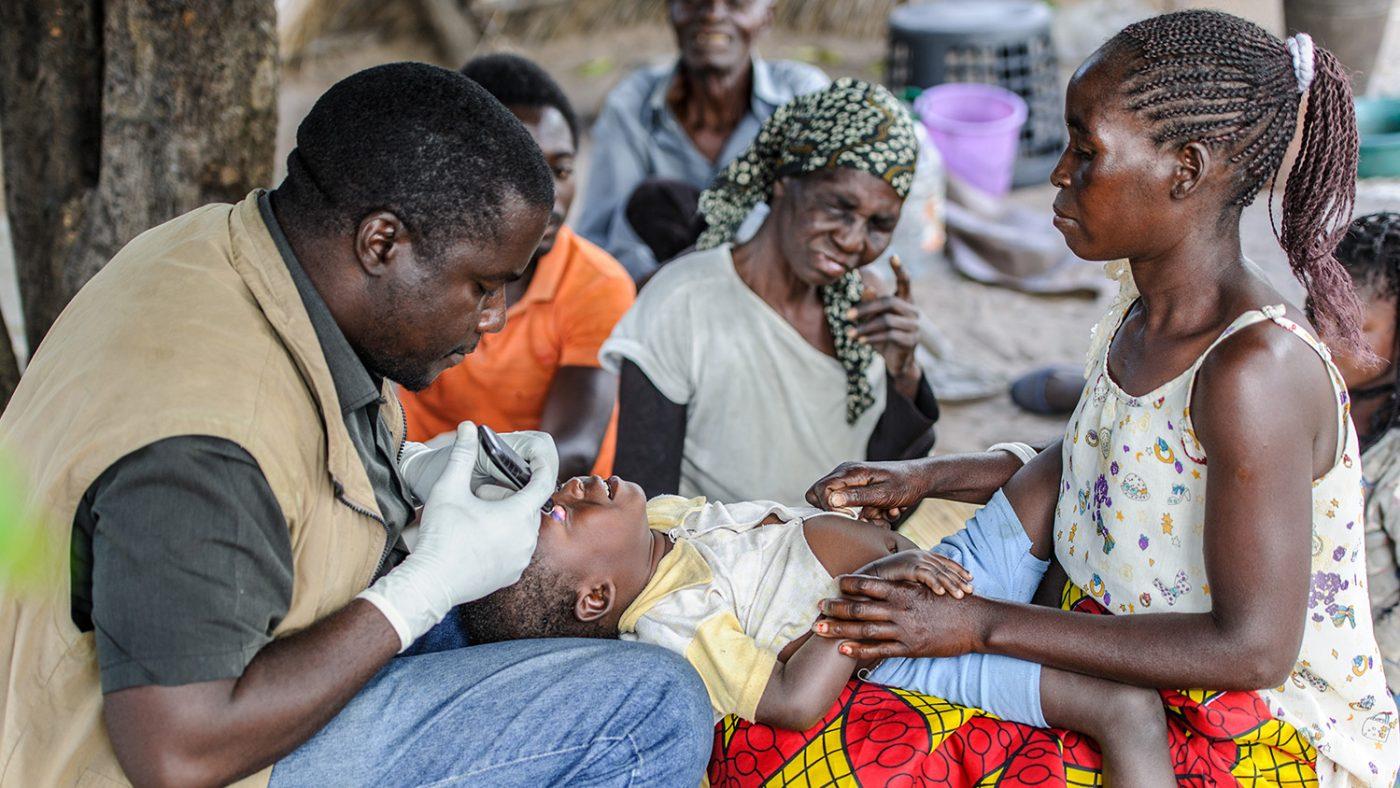 En mor hjelper Mr Ndalela å holde babyen hennes i ro slik at han kan undersøke barnets øyne.
