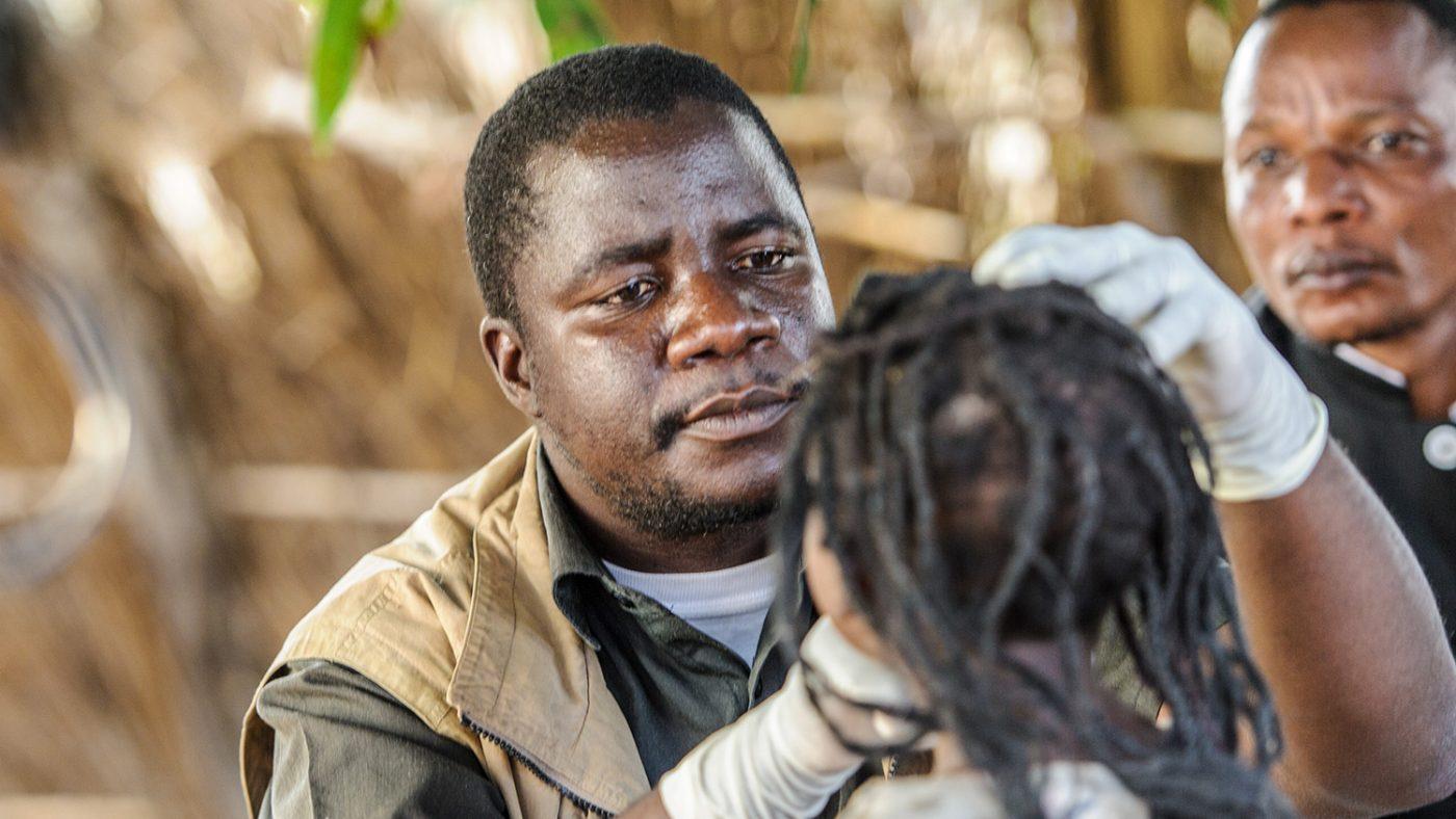 Et nærbilde av Mr Ndalela som undersøker øynene til en ung jente.