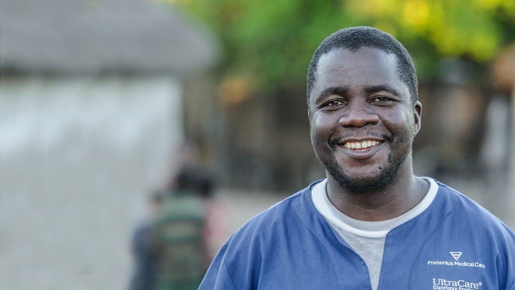 Mr Ndalela står i legeuniformen sin og smiler bredt til kamera.
