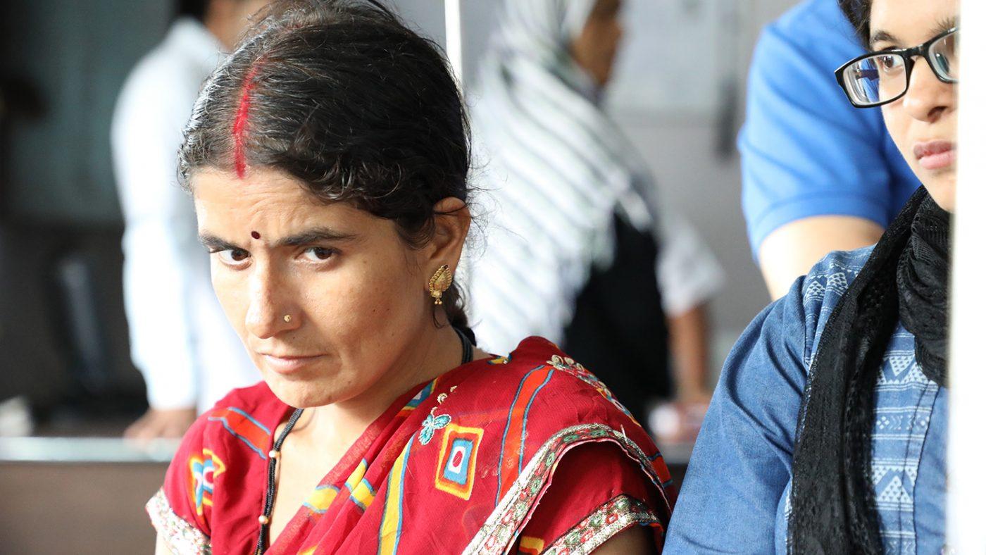 Chandrakala sitter alene – det ser ut som hun er i dype tanker.