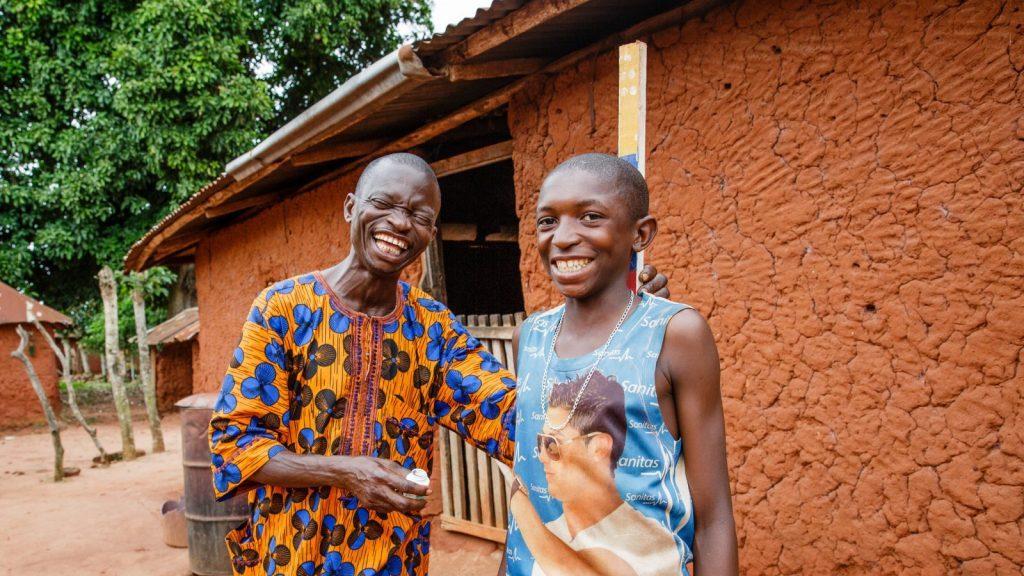 To menn smiler og ler. En av mennene måles mot en doseringspåle.