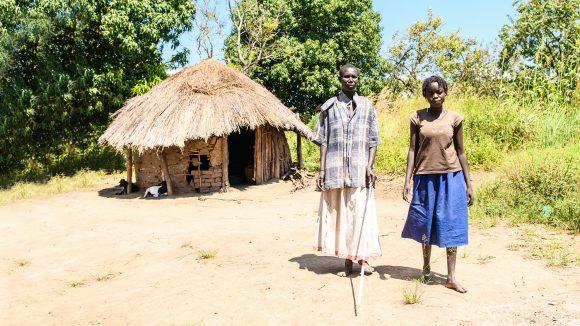 Ayenyo og Lawino står sammen utenfor deres hytte i Uganda.