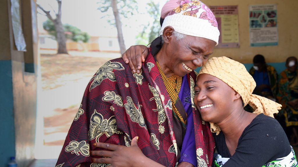 A patient in Tanzania hugs her granddaughter following cataract surgery.