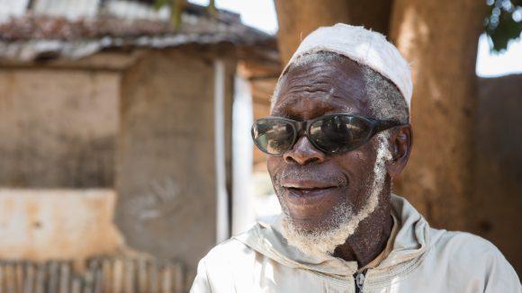 En mannlig trakompasient sitter ute og smiler.