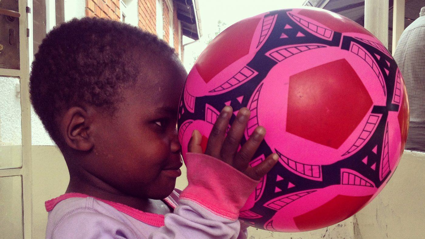 Criscent holder en knallrosa ball foran øynene sine og ser på den.